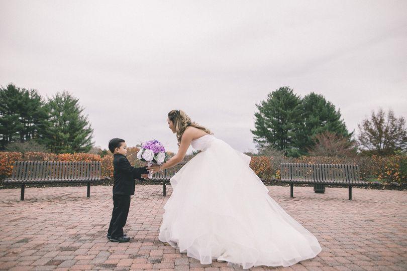 Little boy hands the bride her bouquet