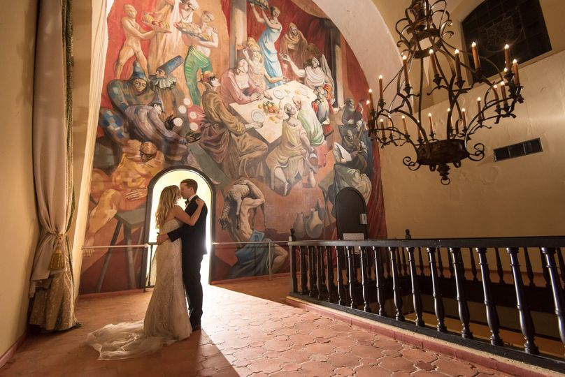 Newlyweds kissing by the mural