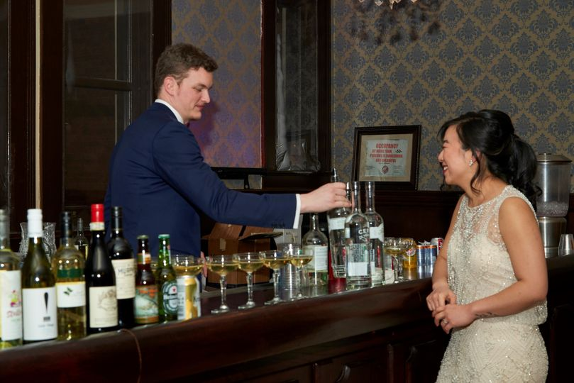 Groom fixing his Bride a drink