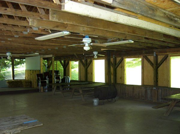 There is a small stage, ceiling fans, electric out-lets, and a large barrel wood stove.  Pic-nic...