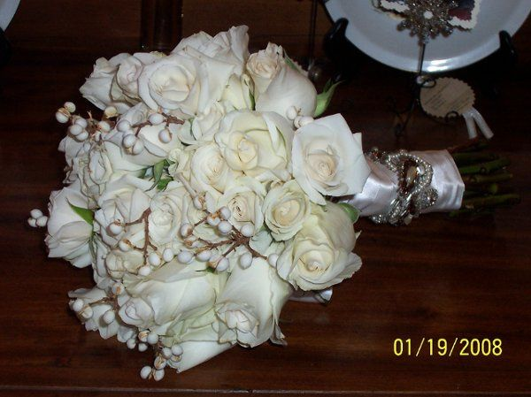 A bouquet of ivory Vendella roses and ivory spray roses with tallaberry, all hand tied in silk satin...