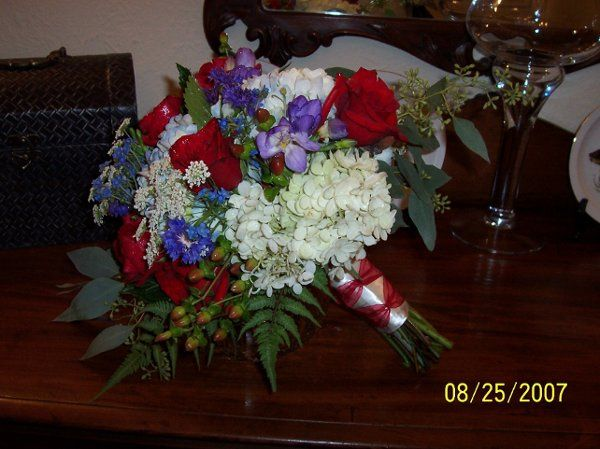 A casual hand tied bouquet of Queen Anne's lace, roses, delphinium, blue corn flower, hydrangea,...
