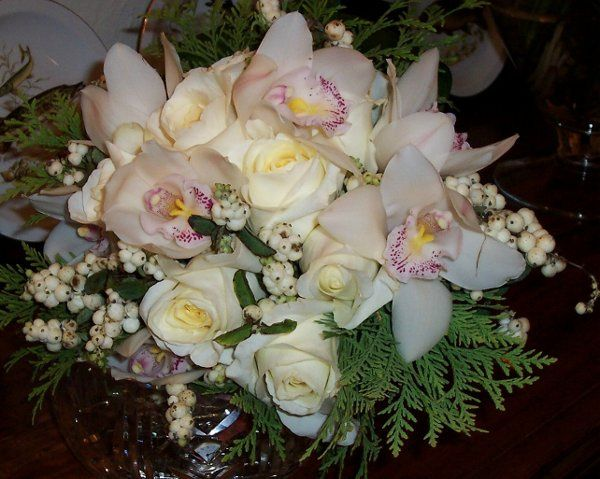 Cymbidium orchids, ivory roses, snow berries and evergreen sprigs make an elegant bridal bouquet,...