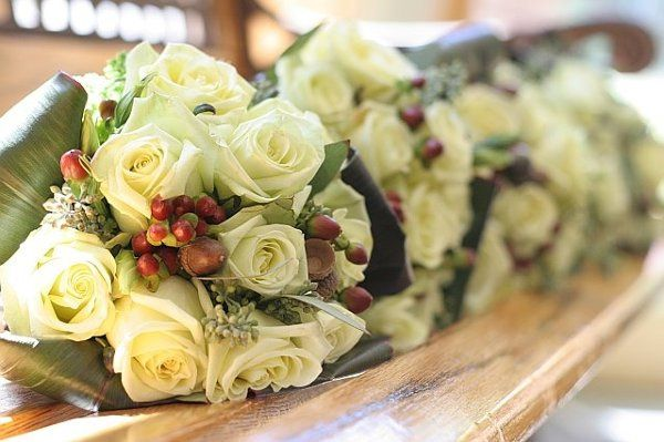 Hand tied bridesmaid bouquets for a fall wedding.  The bouquets are green jade roses, hypericum...