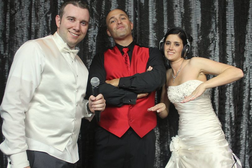 Newlyweds and the DJ at the booth