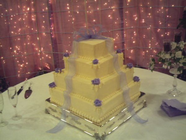 Four tiered pyramid cake with edible roses placed on each corner and a large bow placed as cake...