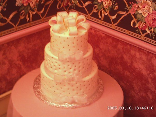 Three tiered traditional wedding cake covered with fondant with silver ribon around the bottom of...