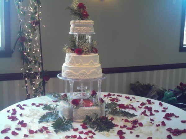 Four tier cake with two sets of columns and water fountain on top of bottom tier. Red rose bouquet...