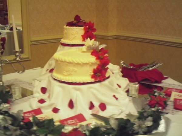 Two seperate cakes, with flowers cascading down on one side, placed atop multi-level stands. The...