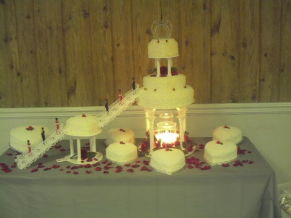 Nine tiers of heart shape cakes of various sizes with columns, double staircases and fountain. Rose...