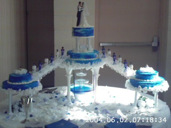 Seven tiered cake with 4 sets of columns, double staircase on both sides, and fountain. Bridal party...
