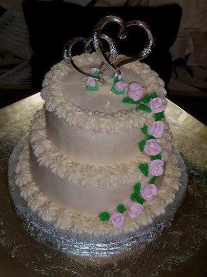 Small Double Tiers Wedding cake with edible pink roses cascading down the side.