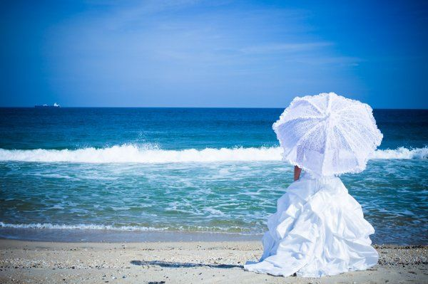 Parasol in hand, the white crest and blue water on sand draws the eye from the waves to crashing...