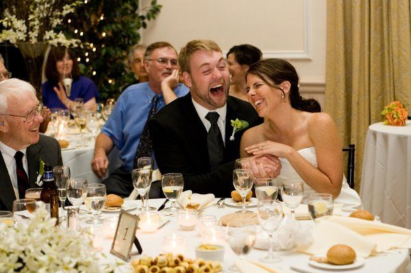 The bride and groom laughing during their reception toasts.