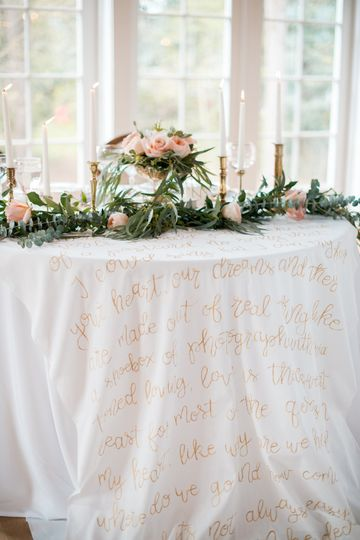 The sweetheart table was adorned with a cascading floral garland, gold flatware and a table linen...