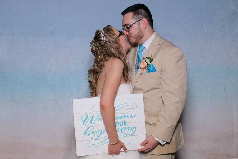 Bride and groom kiss with sign