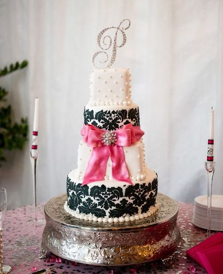 4 tier fondant cake with edible pearls damask pattern and fondant pink bow alternating suare and...