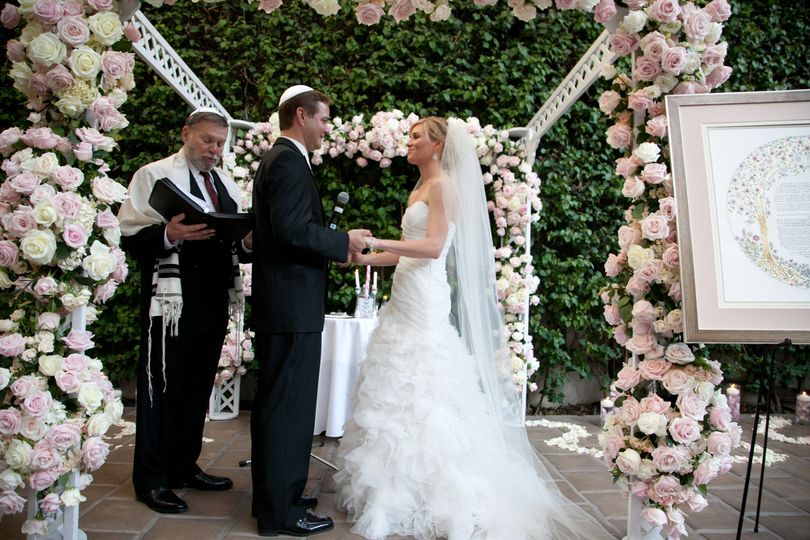 "Note the ""Ketubah"" on display next to the floral chuppah"
