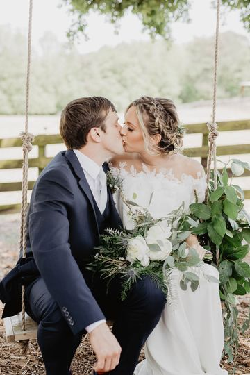 Newlyweds kissing on the swing