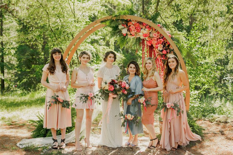 Bride and her bridesmaids by the arch