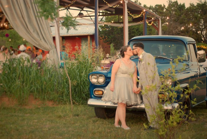 Newlyweds with the pavilion and 1959 Apache pickup truck in the background