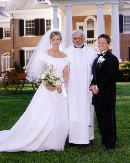 Lovely newlyweds with officiant