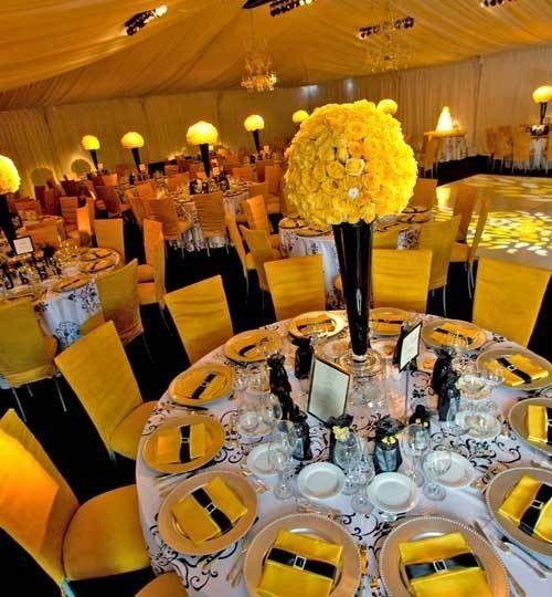 Gorgeous vibrant yellow rose topiary centerpiece atop black crystal vase.