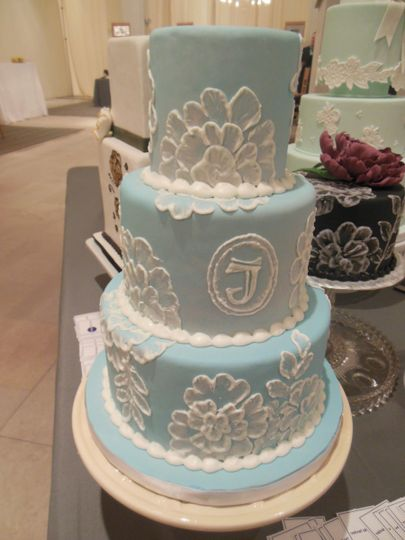 Brushwork on royal icing gives an embroidered look to this three-tiered wedding cake.
