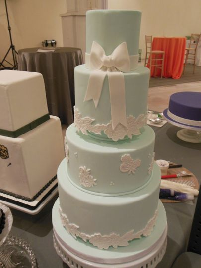 Fondant bow and floral patterns on a four tiered wedding cake