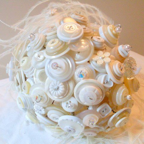 Creme and white button bouquet with ostrich feathers.  A popular choice.  Traditional colors in a...