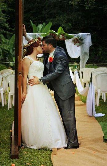 Newlyweds share a kiss on aisle