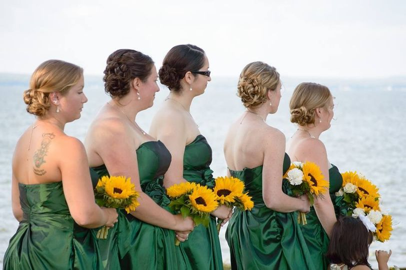 Bridesmaids in green dresses with sunflower bouquets