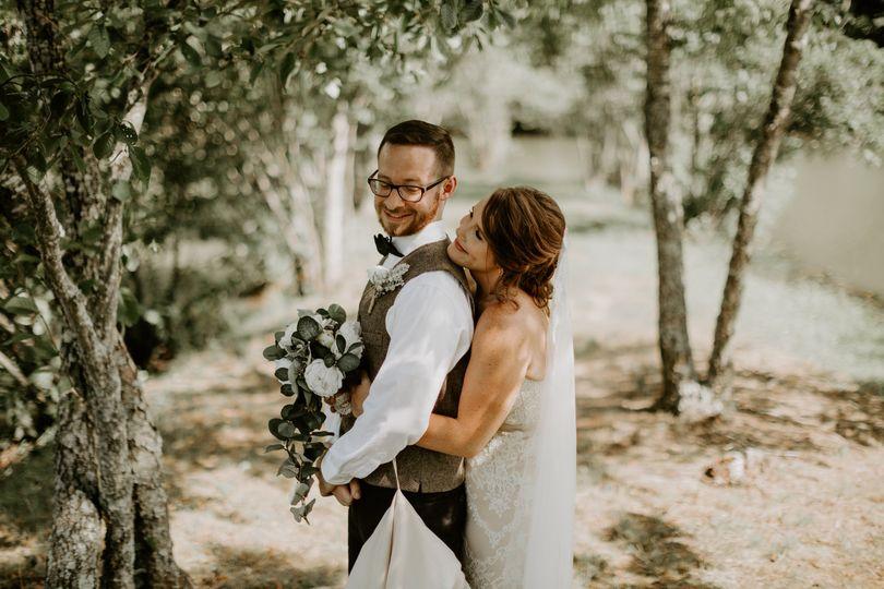 Bride groom embrace under tree