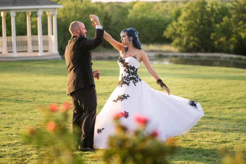 Newlyweds dancing in field