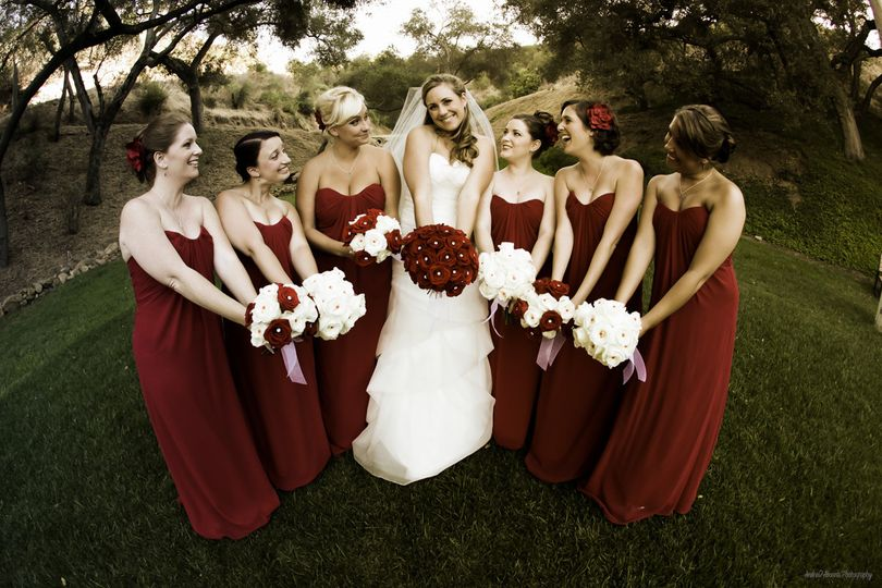 Bride in white with her bridesmaids in red, all holding their bouquets together