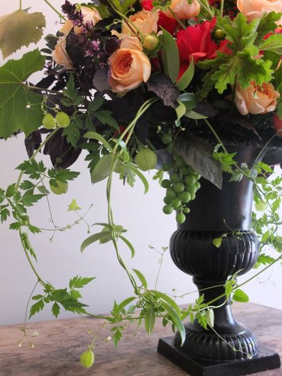 Large Urn with summer flowers and fruit and trailing vine accents