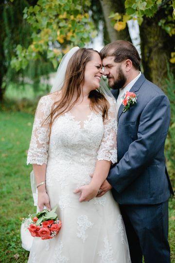 A couple embrace with a bouquet