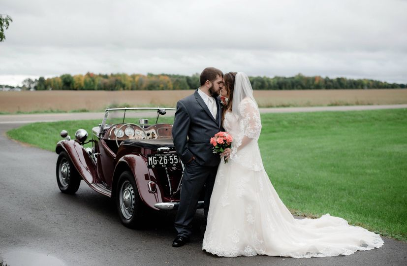 Newlyweds kiss beside a vintage car