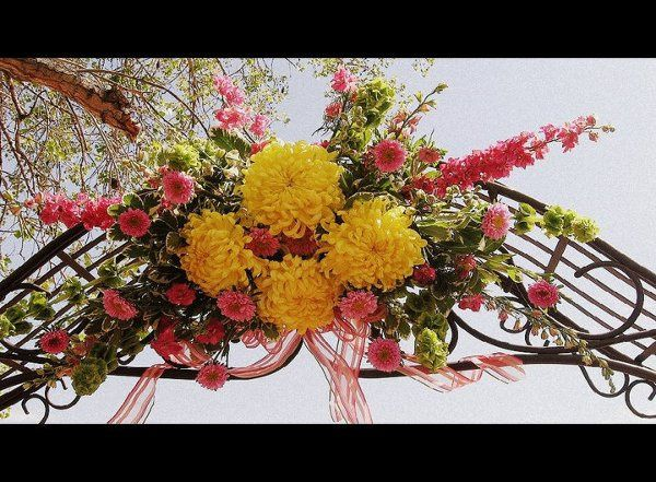 Fuschia and sunshine yellow are used to decorate this arch. Design by Florals by Rhonda.