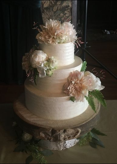 """The new classic"" a butter cream finished cake with fresh flowers and a spiral texture."