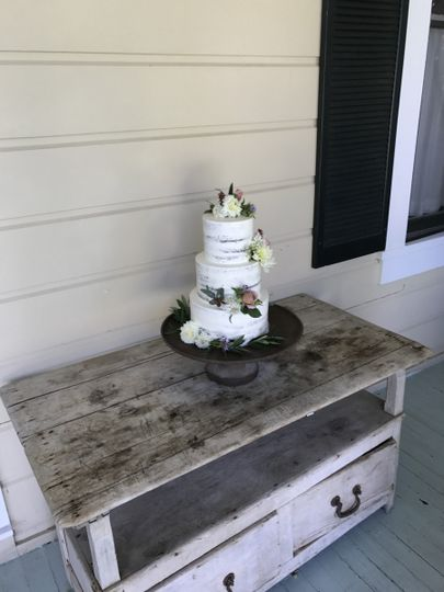The naked style cake on a rustic stand in a beautiful setting.