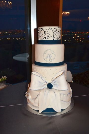 4-tier cake with blue details and ribbon icing