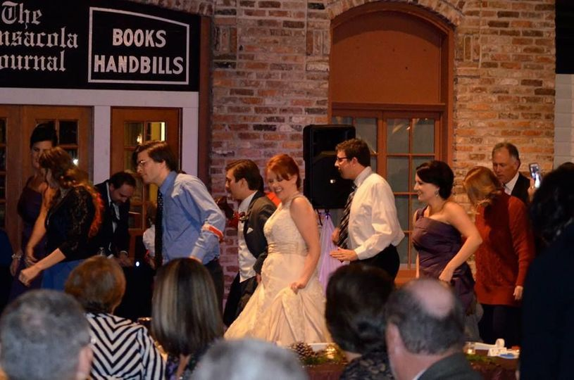 Bride, Groom, and everyone having fun at a wedding reception at the Museum of Commerce in downtown...