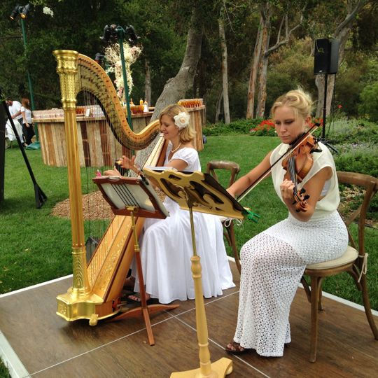 Harp and violin duo provide romantic music for a garden wedding ceremony at San Ysidro Ranch.