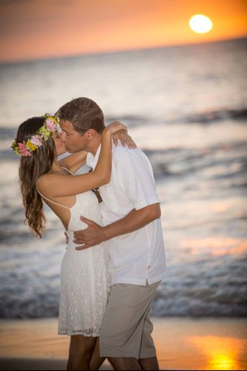 Simple sunset beach wedding on the island of Oahu at the famous north shore. She is wearing a Haku...