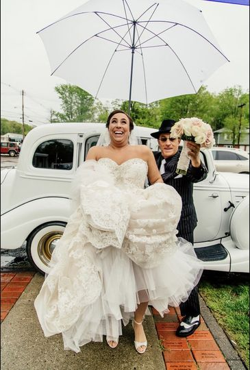 Yes, Danny Has a Huge White Umbrella to Help Keep the Rain drops off of the Bride.