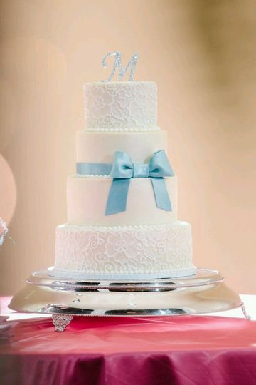 Three tier cake with blue ribbon