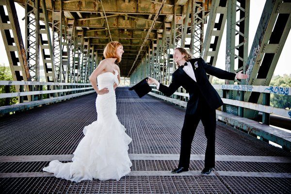 Bride and groom dancing on bridge.
