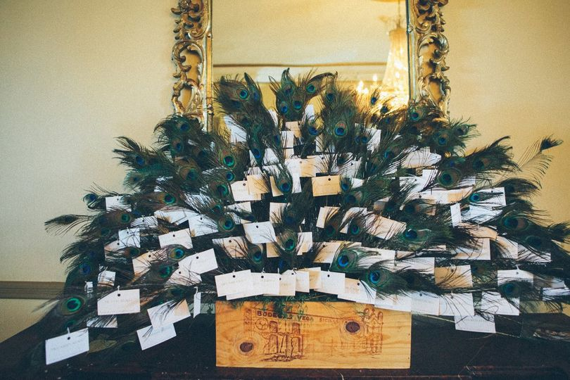 A dramatic escort card display of peacock feathers - one for each guest