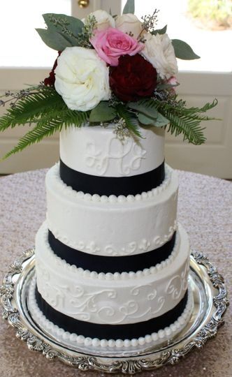 Wedding cake with black ribbons and flowers on top